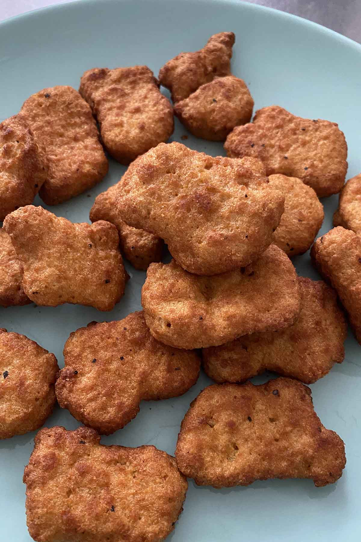 Simulate Chicken Nuggs on a blue plate after air frying