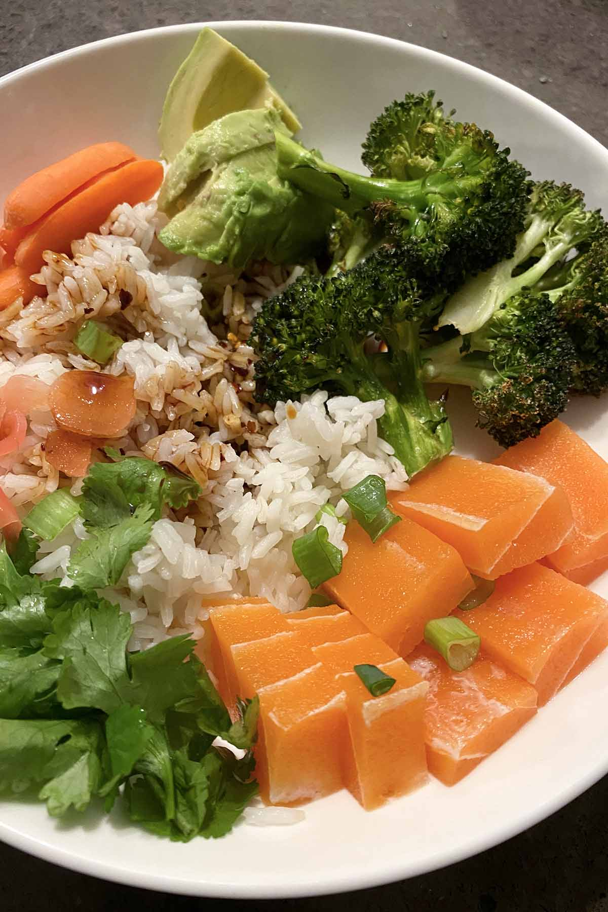 a rice bowl with vegetables, soy sauce, and Vegan Zeastar salmon