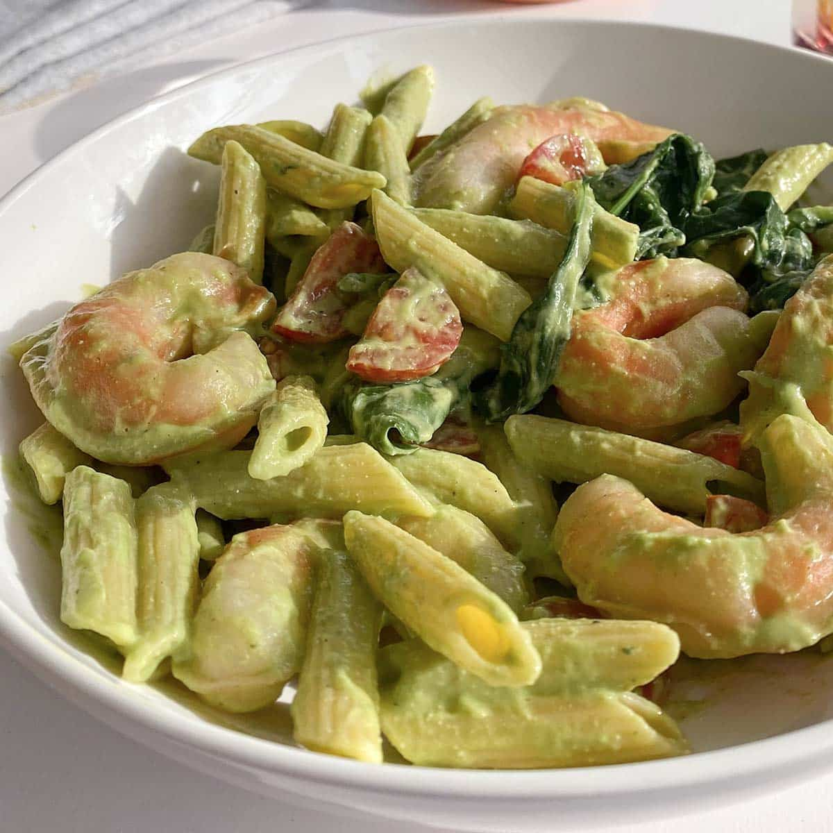 pesto pasta with vegan shrimp, baby kale, and tomatoes