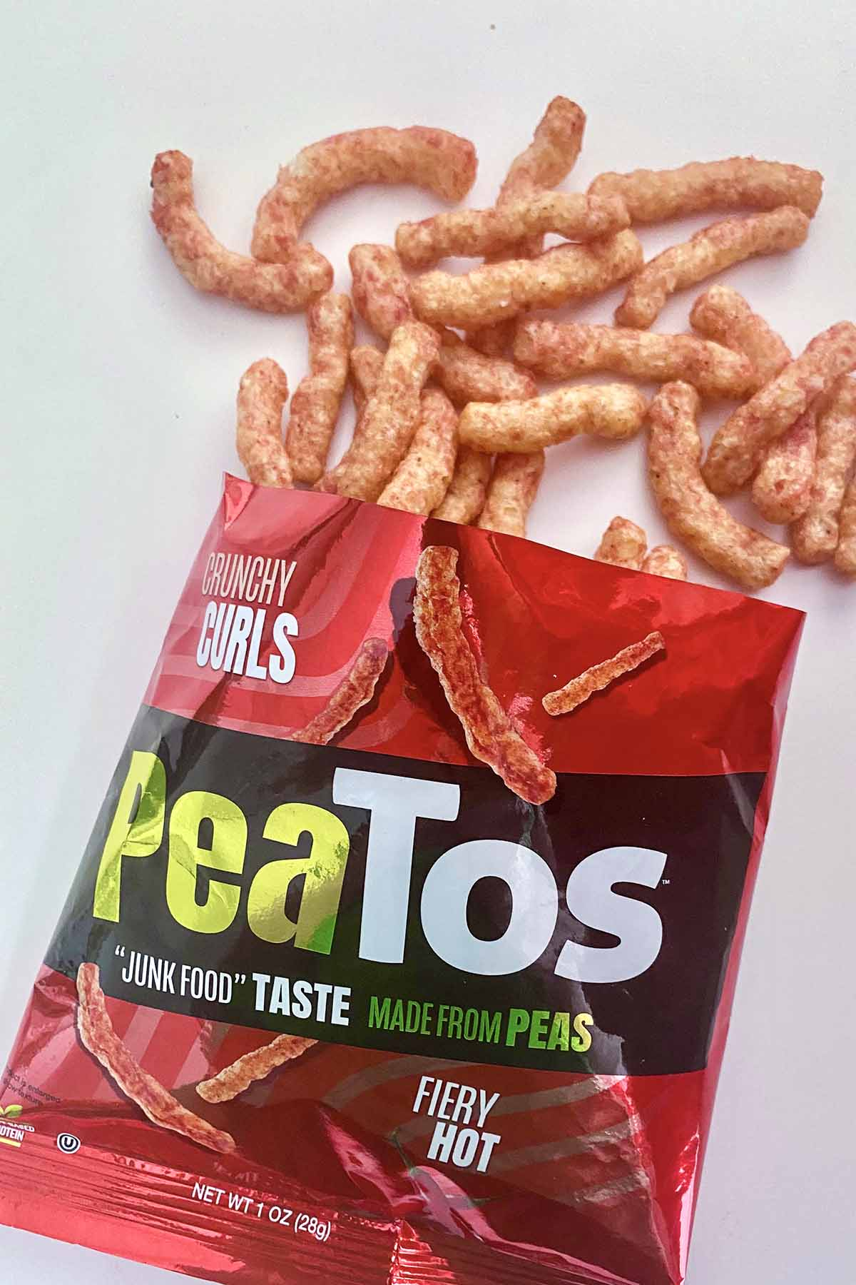 an open bag of Fiery Hot Peatos with pieces spilling out onto a white table
