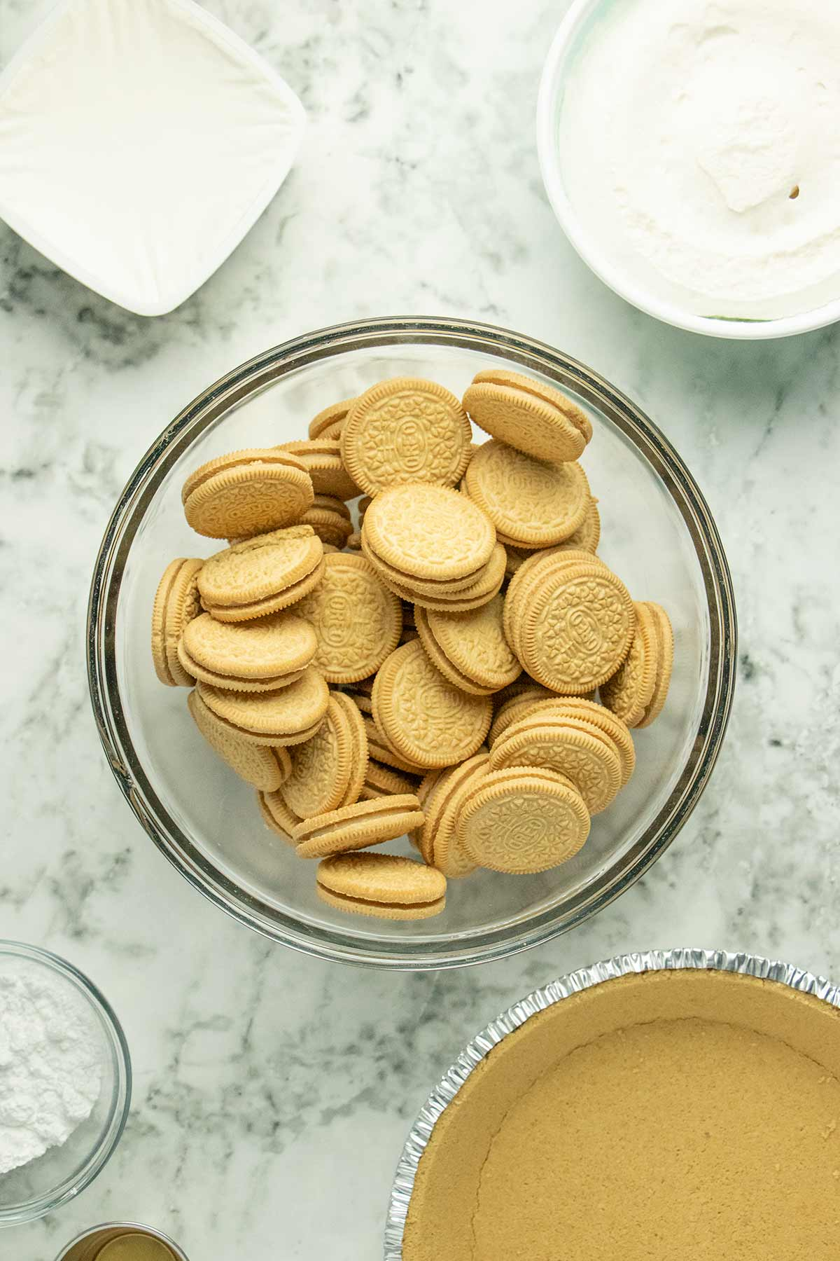 bowl of Golden Oreos on a marble table surrounded by the other pie ingredients