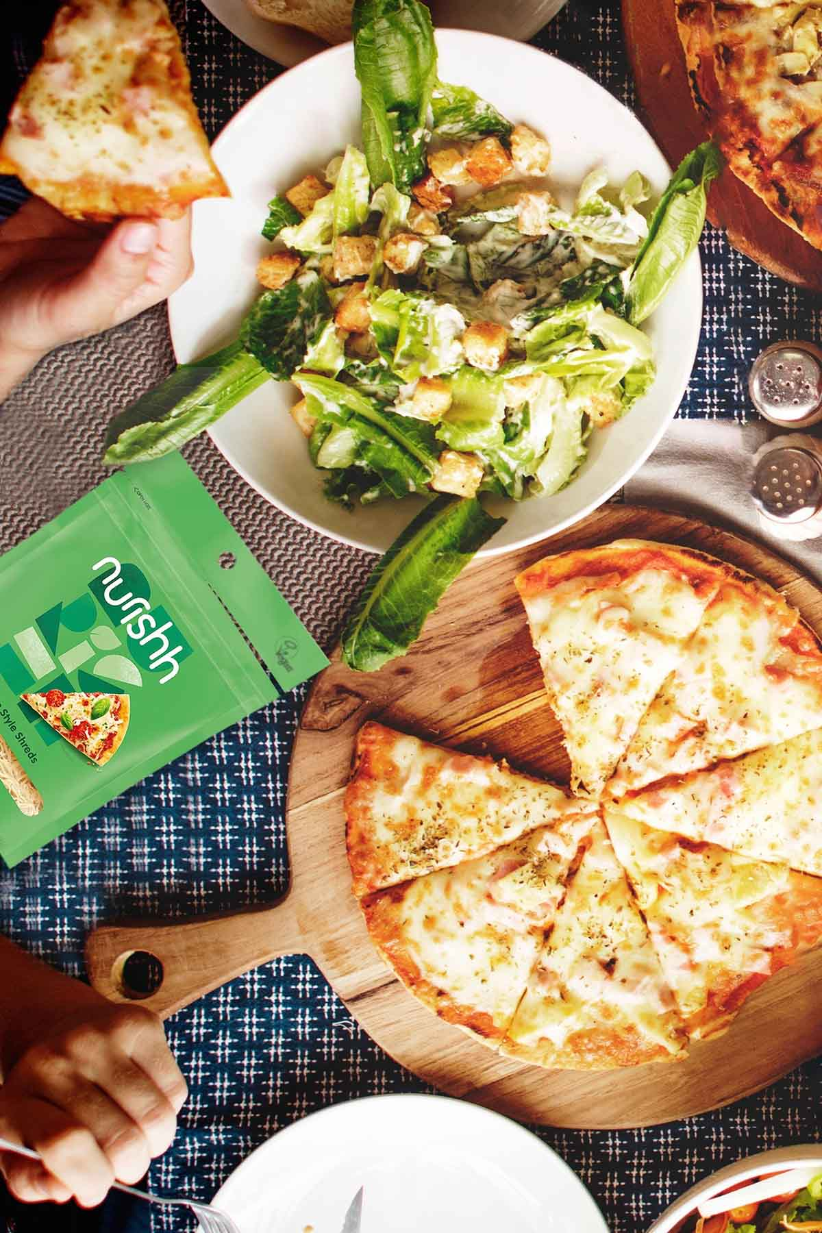 image of a salad and pizza with Nurishh vegan cheese