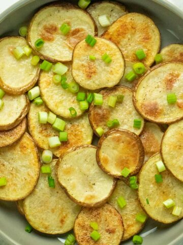 serving plate of crispy, baked sliced potatoes topped with chopped green onions
