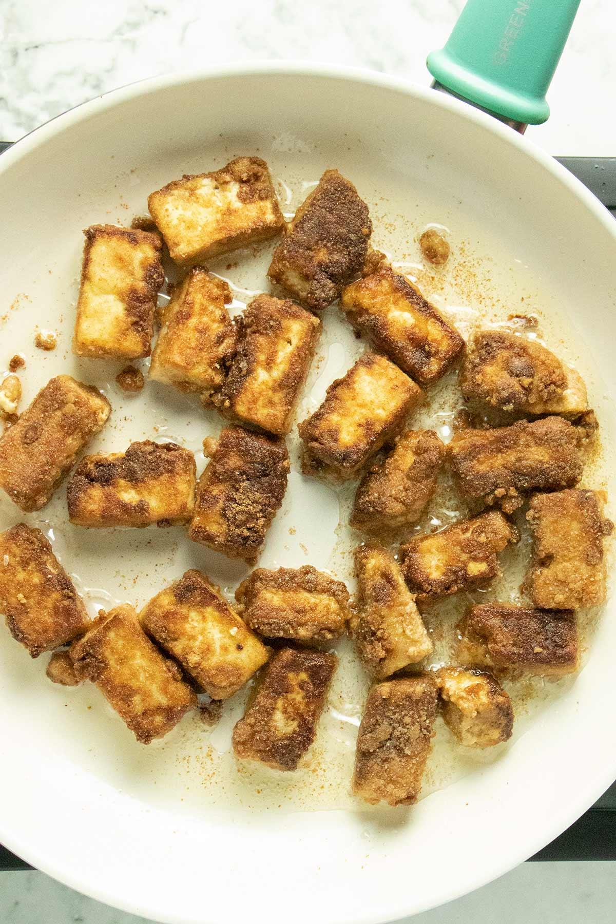 frying tofu in a white pan