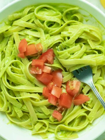 bowl of fettuccine with avocado pesto and tomatoes