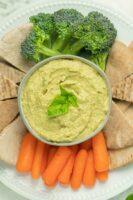 pesto hummus in a serving dish surrounded by pita points and vegetables