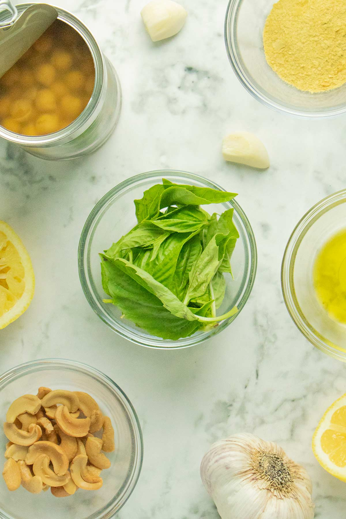 basil, chickpeas, and other basil hummus ingredients on a marble table