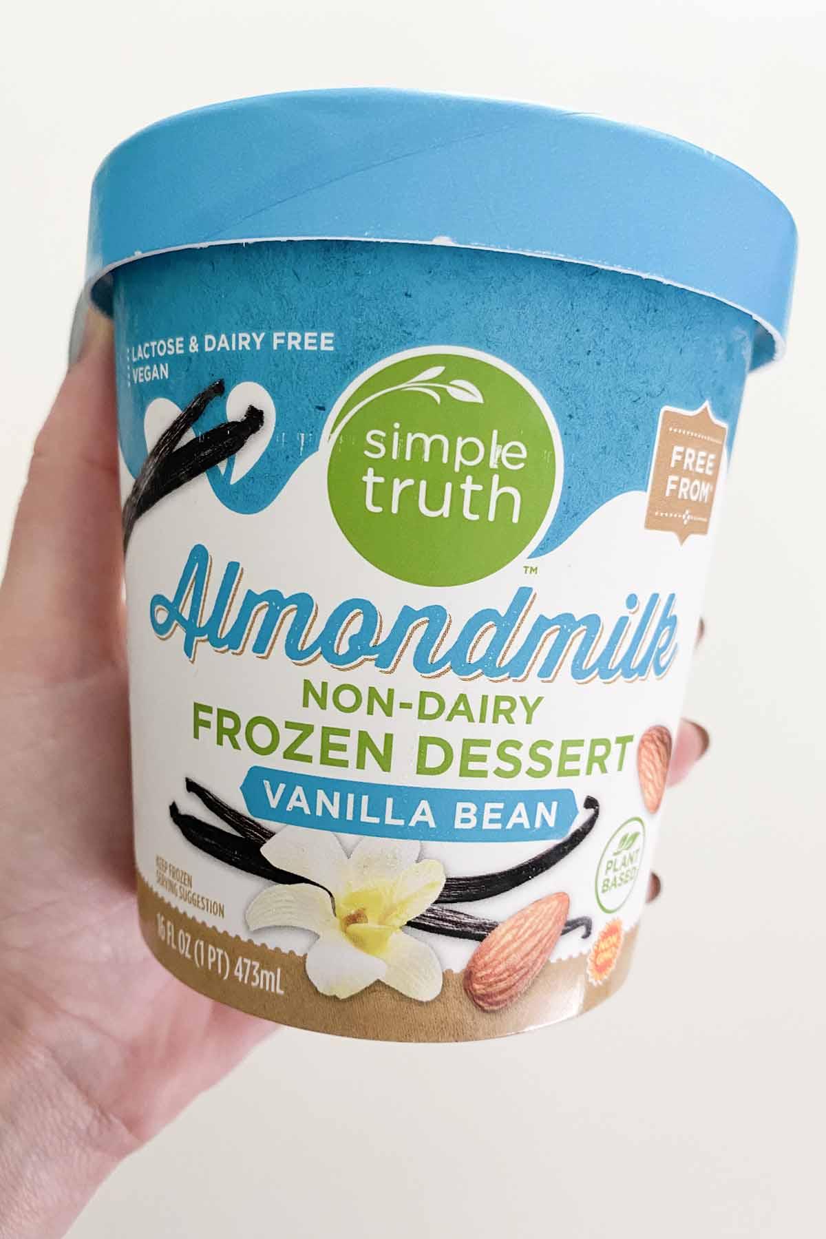 hand holding a pint of Simple Truth™ Vanilla Bean Almond Frozen Dessert