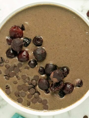 chocolate smoothie bowl topped with frozen cherries and chocolate chips