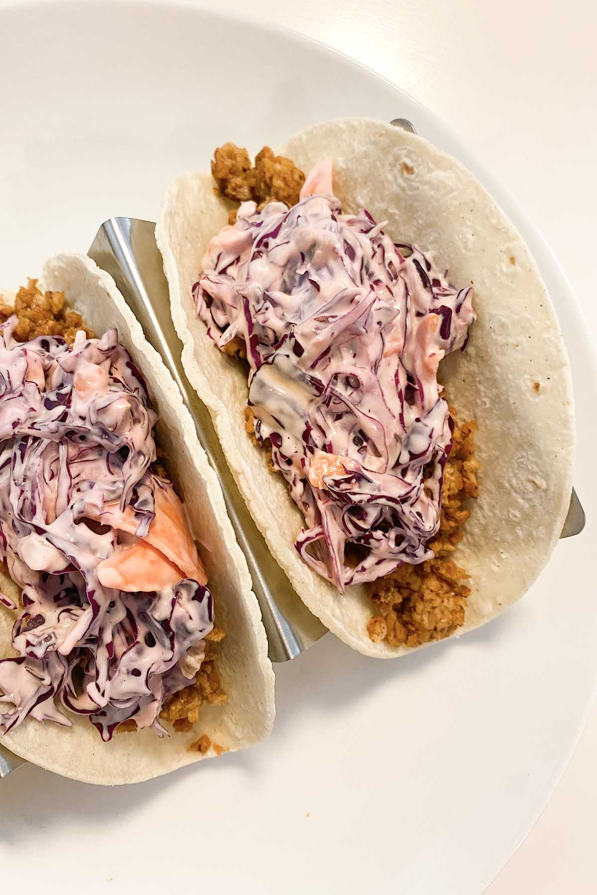 overhead photo of Deliciou Plant Based Pork Tacos topped with purple slaw on a white plate