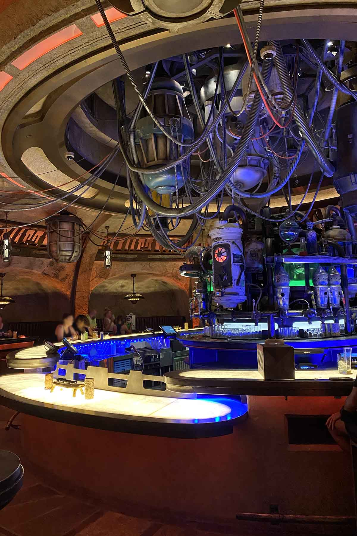 a futuristic-looking bar with lots of exposed cables and colored lighting