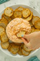 hand dipping a cracker into a serving bowl of vegan pimento cheese
