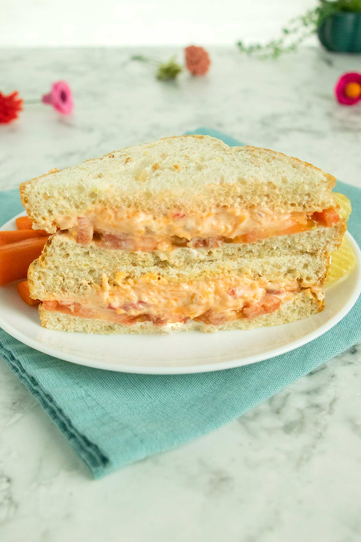 vegan pimento cheese sandwich on a white plate with carrots and chips on the side