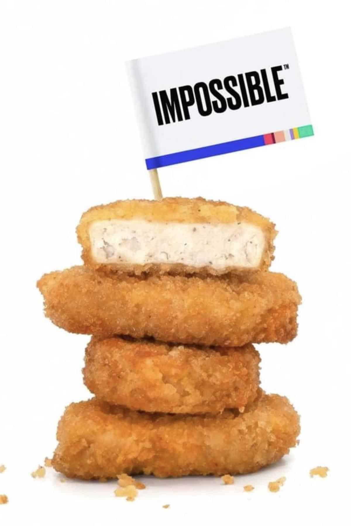 stack of Impossible vegan chicken nuggets on a white background with an Impossible paper flag in the top one
