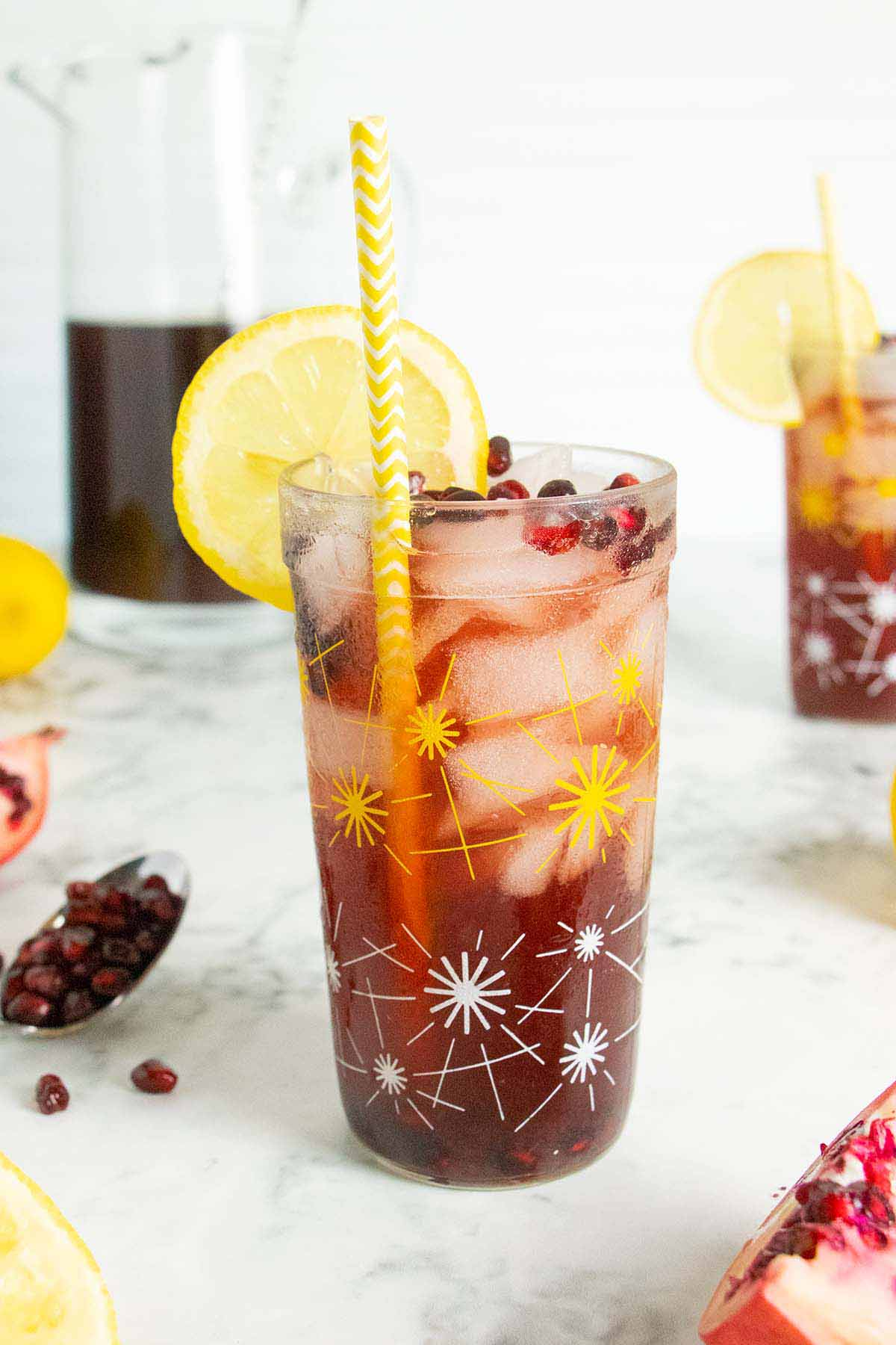 glasses of pomegranate lemonade on a table with a pitcher