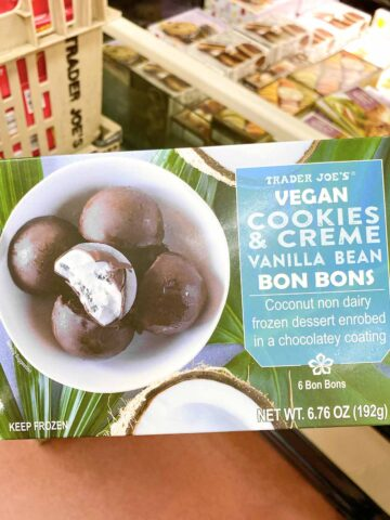 Hand holding a box of Trader Joe's Vegan Cookies & Cream Bon Bons in a grocery store aisle