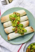 blue plate of air fryer taquitos topped with avocado salad