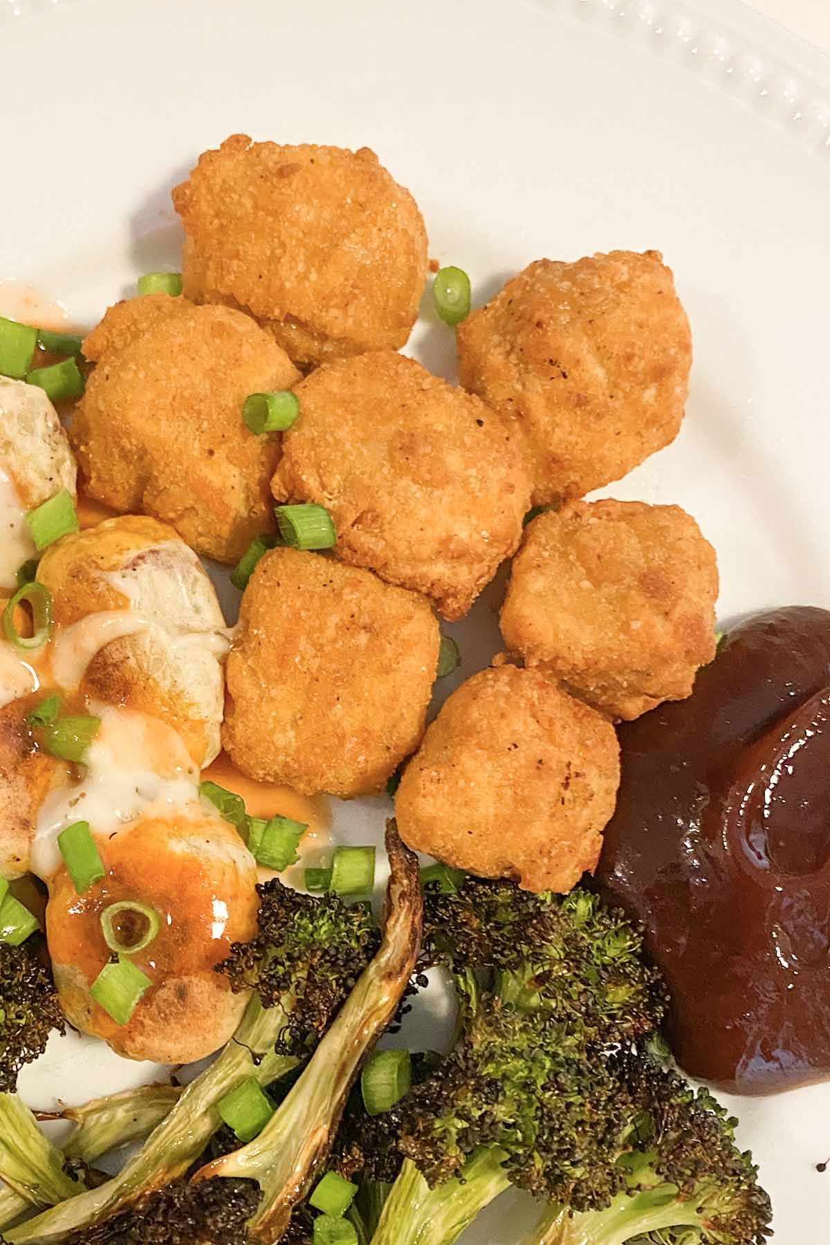 Gardein Ultimate Plant Based Chick'n Nuggets on a white plate with potatoes and broccoli