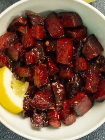 air fryer beets with a lemon wedge in a white bowl