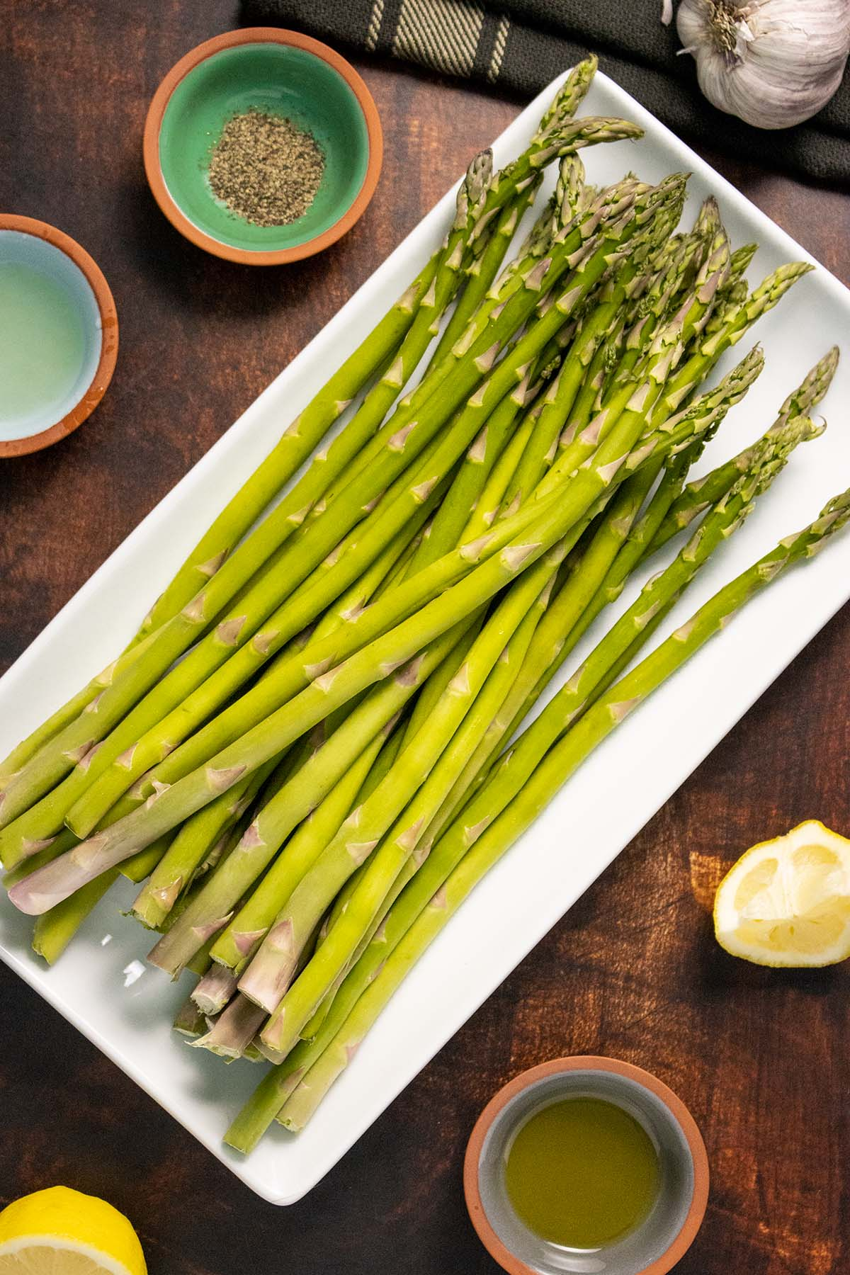 uncooked asparagus on a plate surrounded by garlic, lemon, oil, and black pepper in small bowls