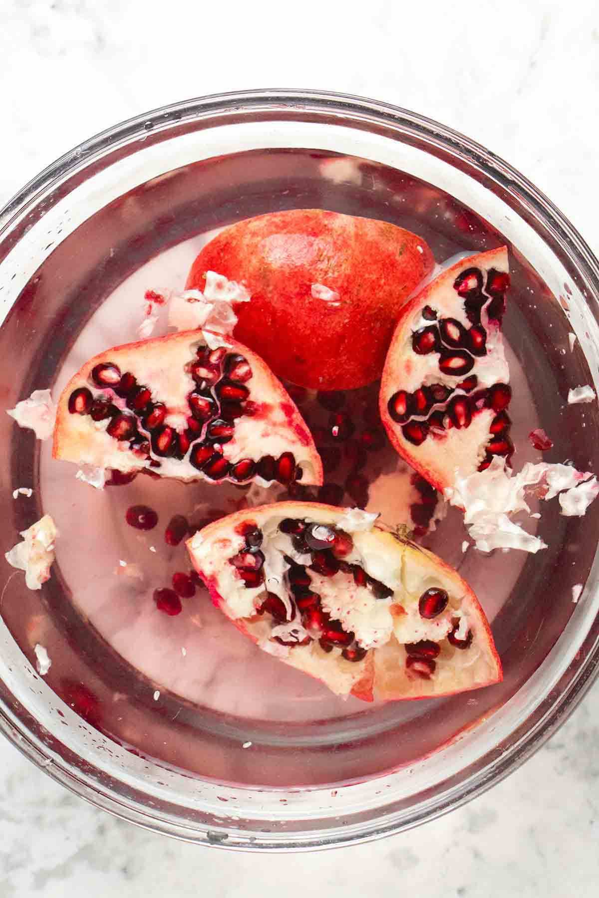 pomegranate pieces floating in a bowl of water