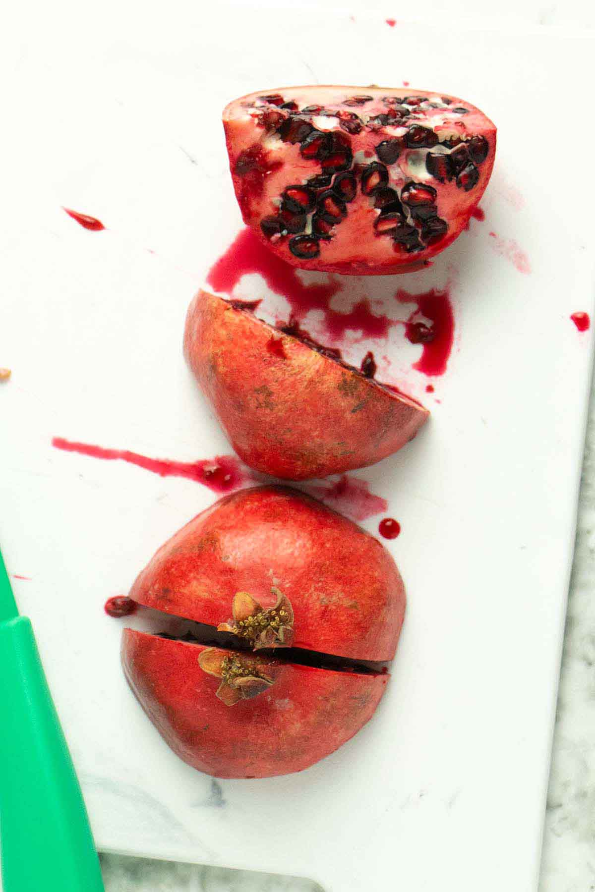 sliced pomegranate on a white cutting board