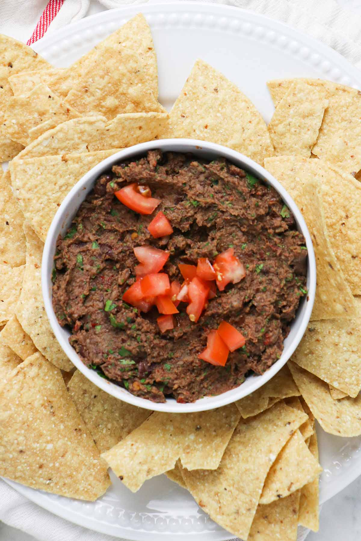black bean dip in a bowl surrounded by tortilla chips