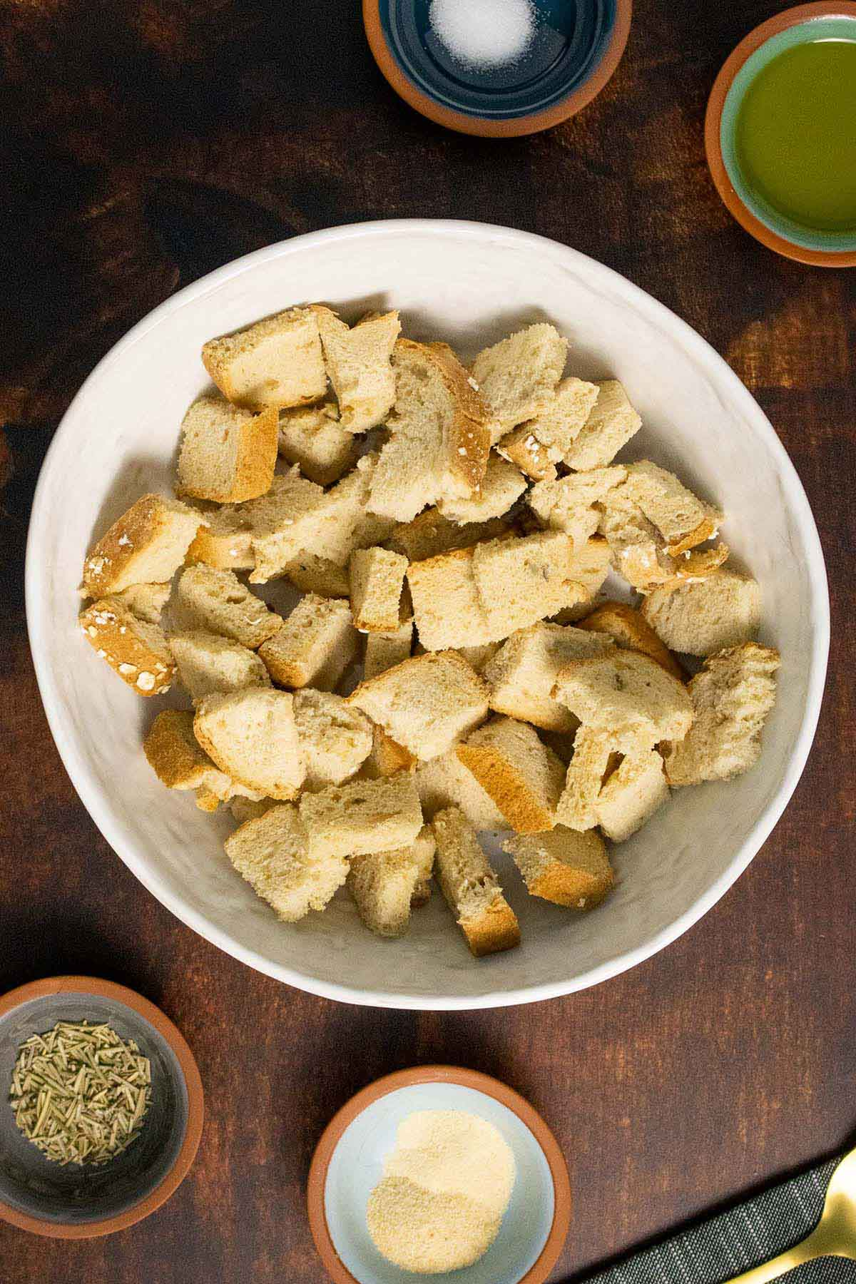 bread cubes and seasonings in bowls on a wood table