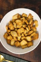 air fryer croutons in a white bowl on a wood table