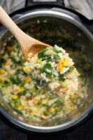 wooden spoon full of risotto over an Instant Pot
