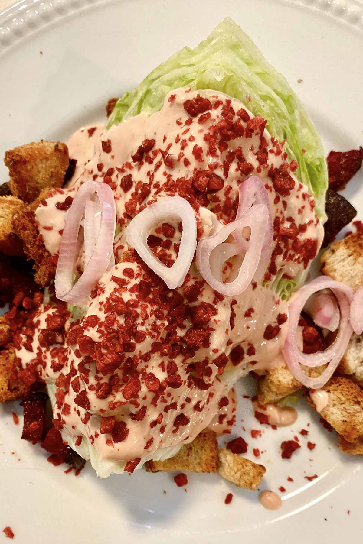 wedge of iceberg lettuce on a plate with Russian dressing, beets, Bacos, croutons, and pickled onions