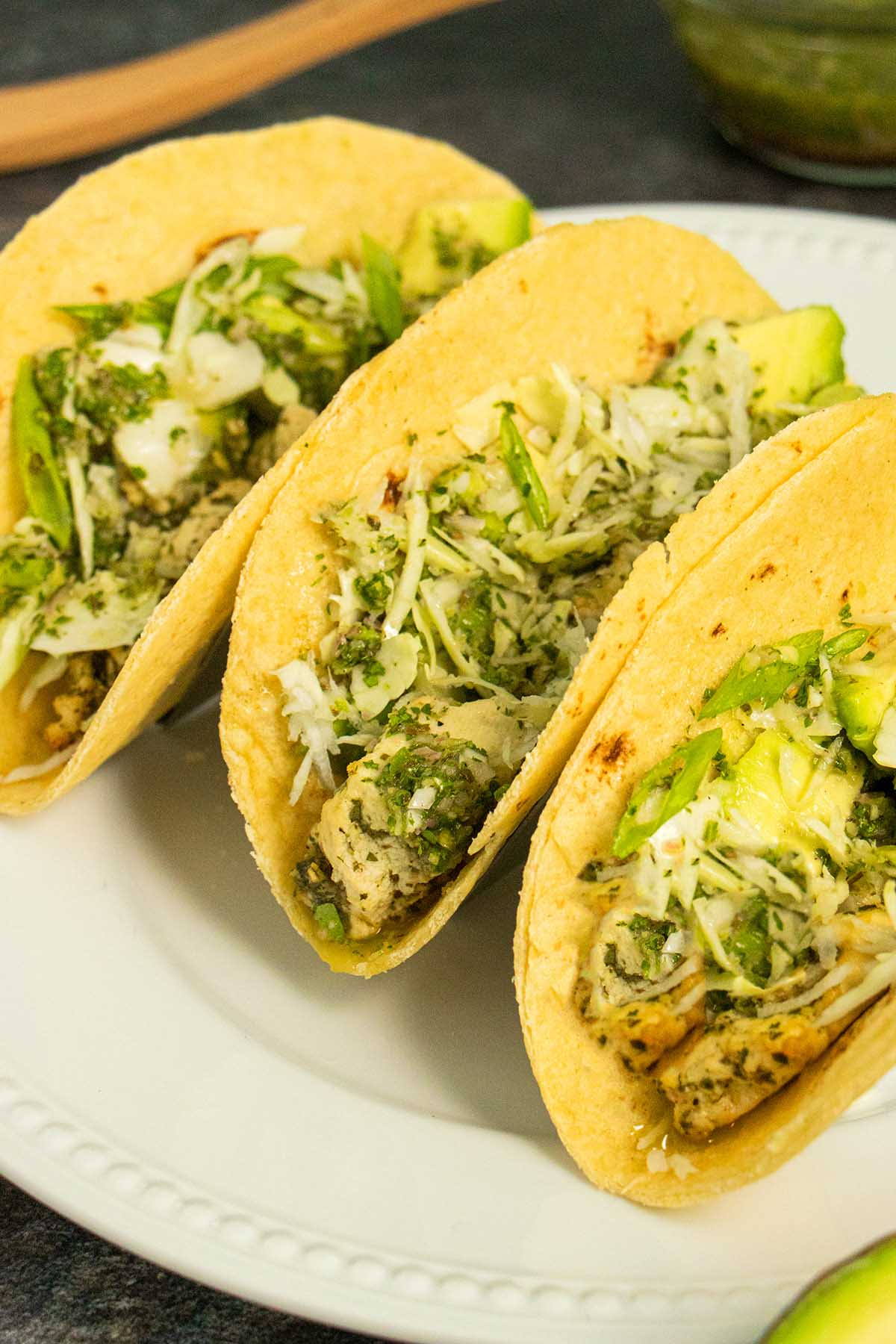 vegan tacos on a white plate with cabbage, avocado, and chimichurri sauce