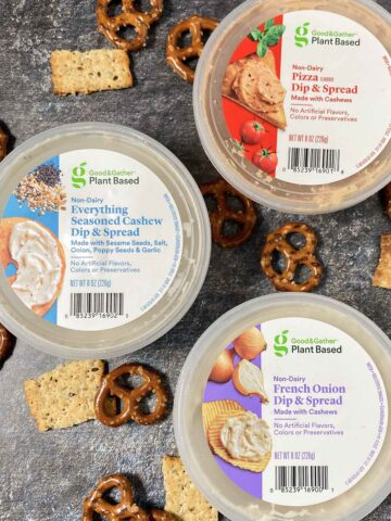 three containers of Good & Gather Plant Based Dip + Spread: pizza, everything bagel, and French onion on a table with pretzels and crackers