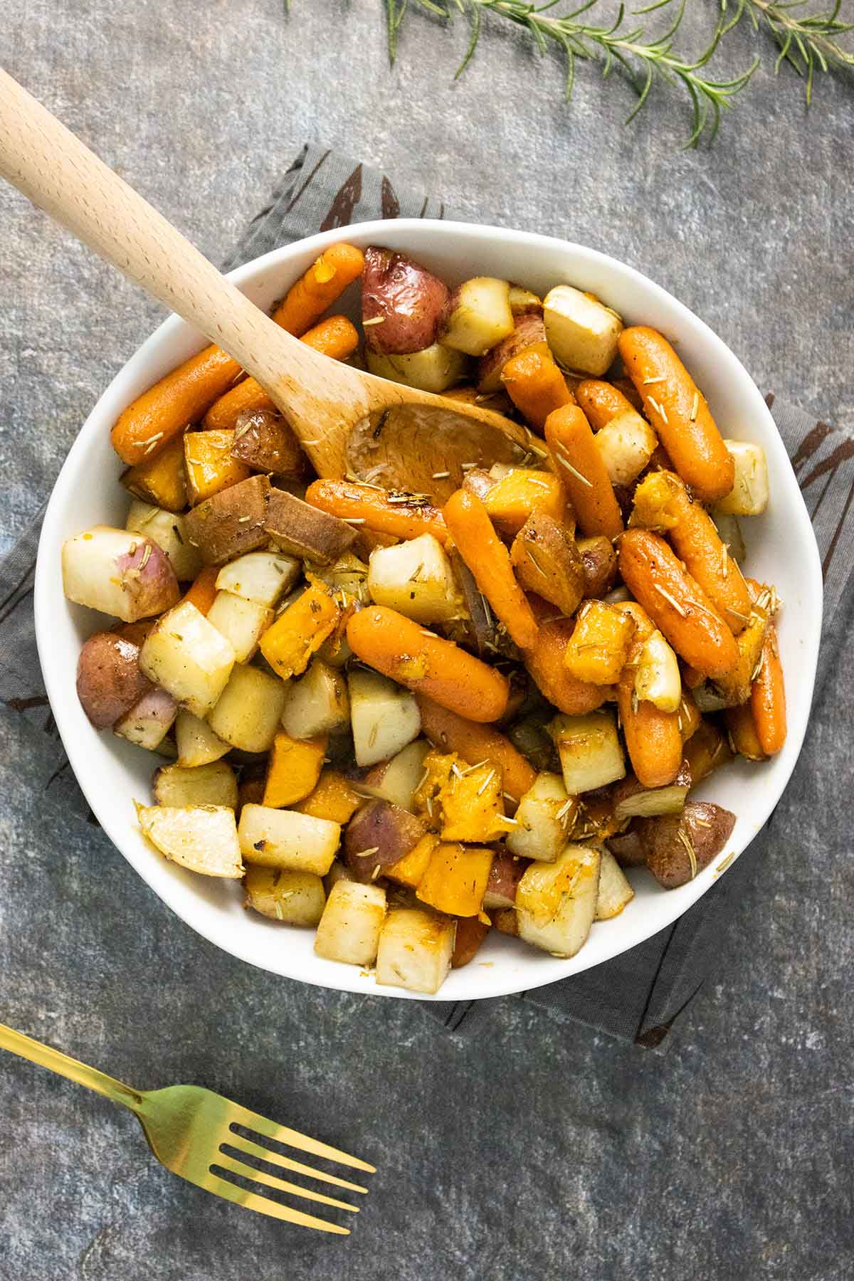 white serving bowl of maple roasted root vegetables with a wooden serving spoon