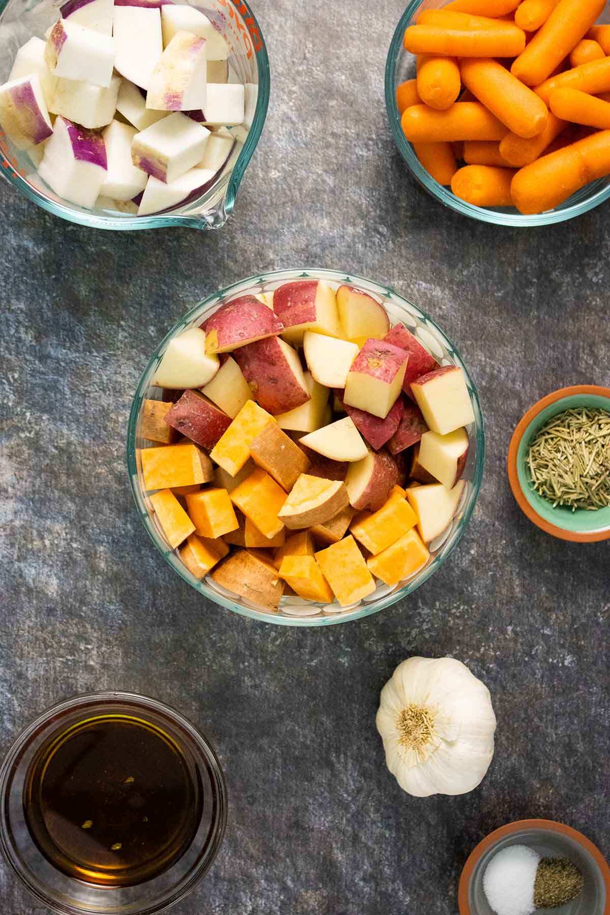 diced root vegetables in glass bowls with other ingredients on a granite countertop