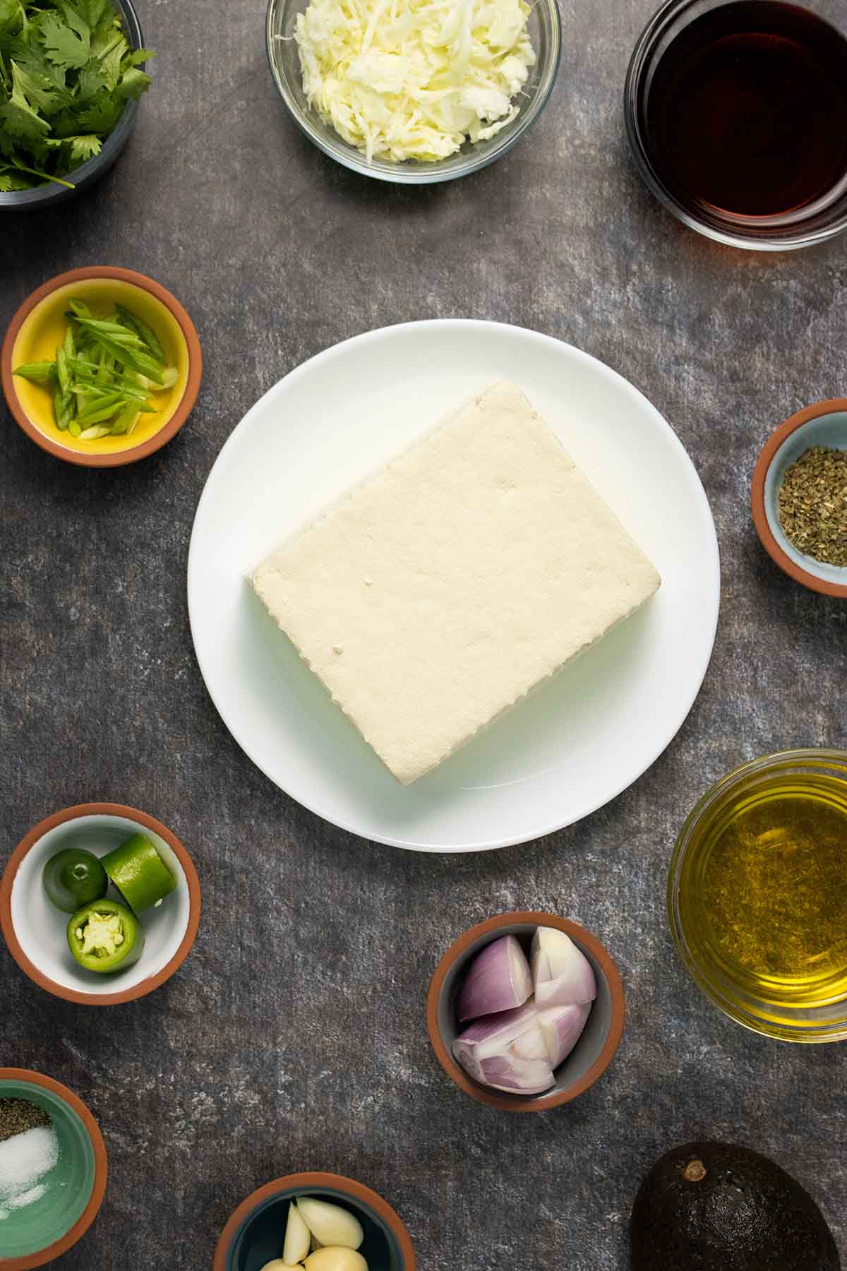 block of tofu on a plate surrounded by chimichurri sauce ingredients