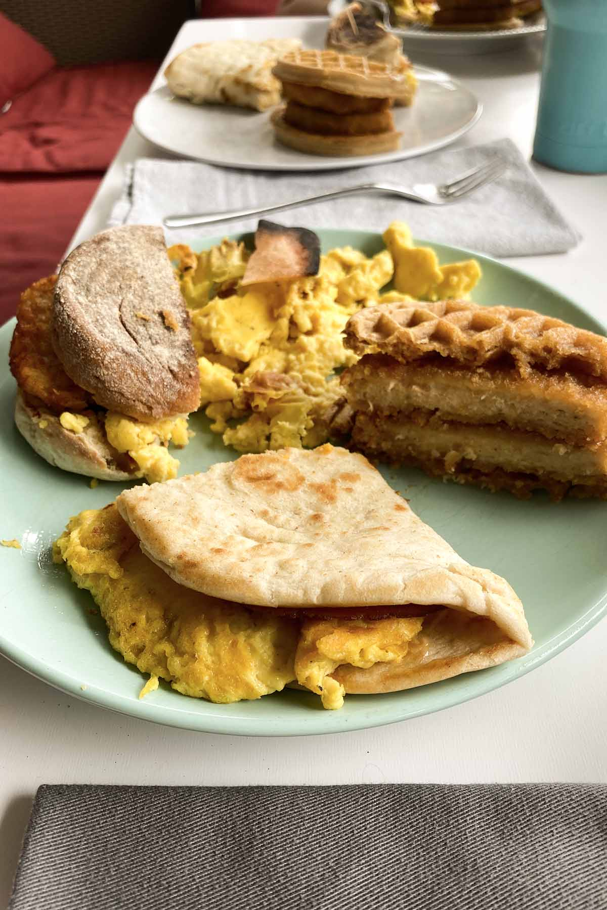 blue plate with three vegan breakfast sandwiches on it