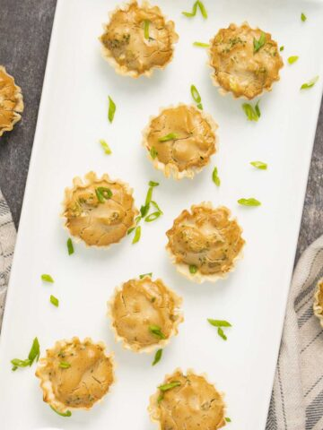 vegan mini quiche on a white serving plate with green onions scattered on it