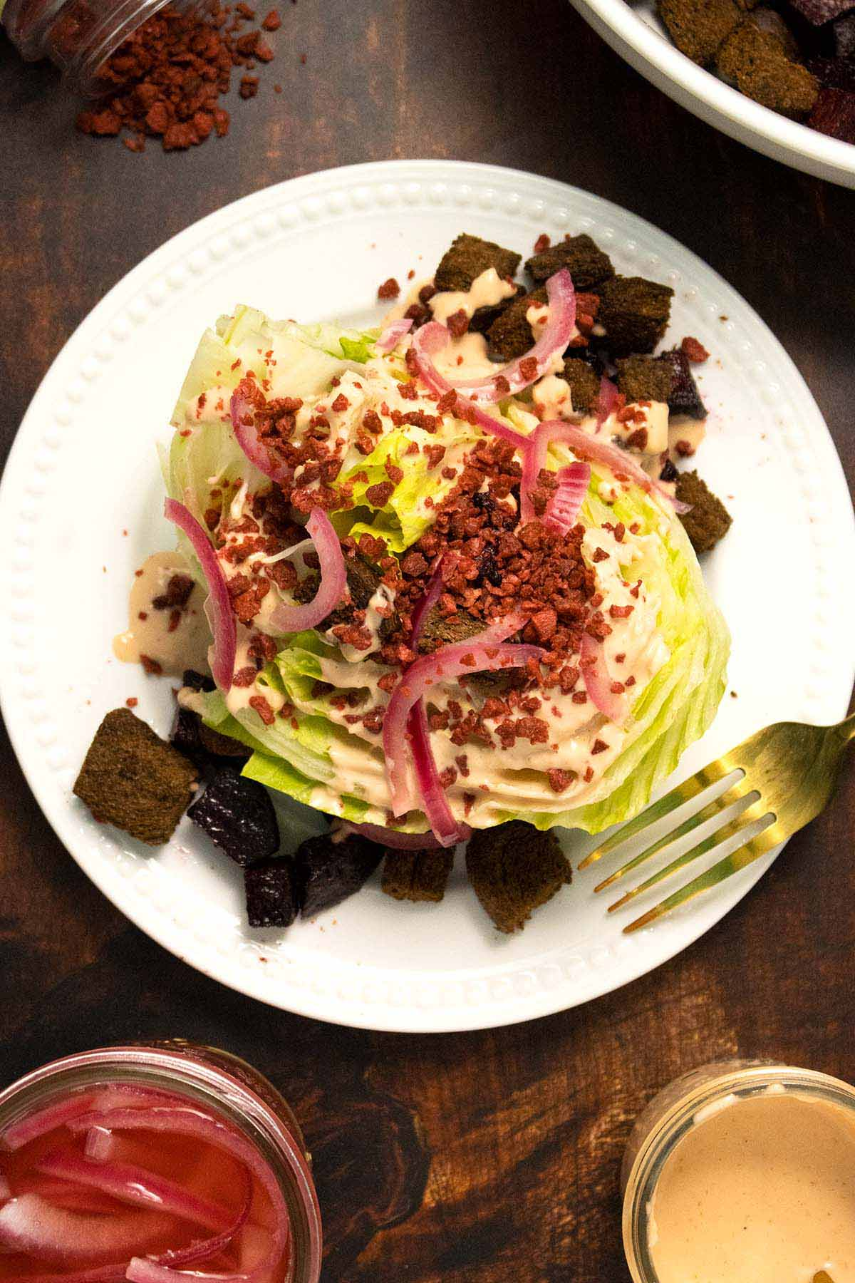 vegan wedge salad with dark croutons, pickled onions, bacon, and creamy dressing on a white plate